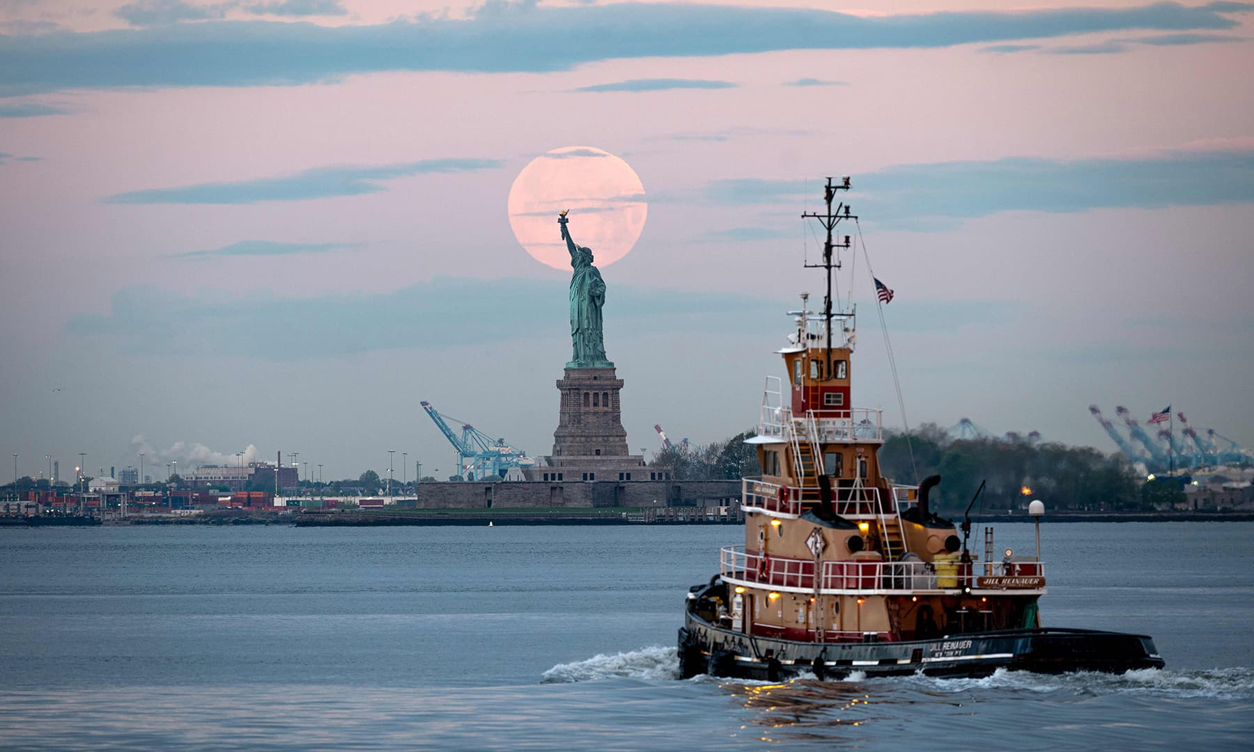 May's full moon sets behind the Statue of Liberty on May 7 in New York City. — AFP