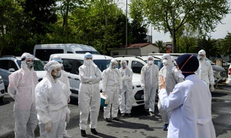 Melek Nur Aslan, right, director of the public health agency in Fatih district, briefs her staff. — AFP
