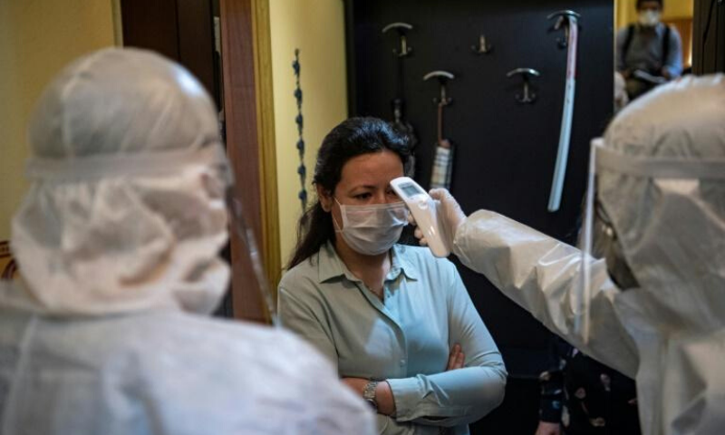 """A health officer checks the temperature of an Istanbul resident. Nearly 6,000 teams of """"tracers"""" track potential cases of the novel coronavirus 24 hours a day. — AFP"""