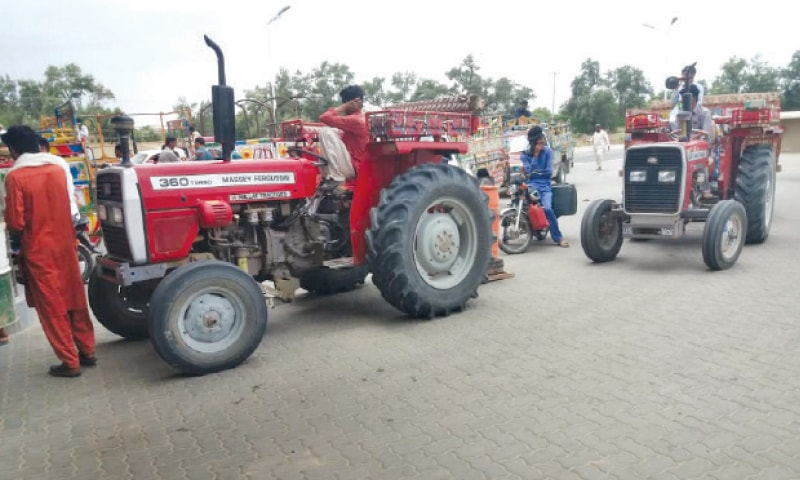 LAHORE Tractor-trolleys line up at a filling station near Bhakkar for getting their tanks filled with diesel. Demand for fuel increases during wheat harvest. — Dawn