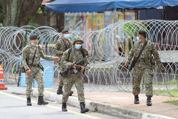 Petaling Jaya (Malaysia): Soldiers wearing face mask patrolling a coronavirus-hit area on Sunday.—AP