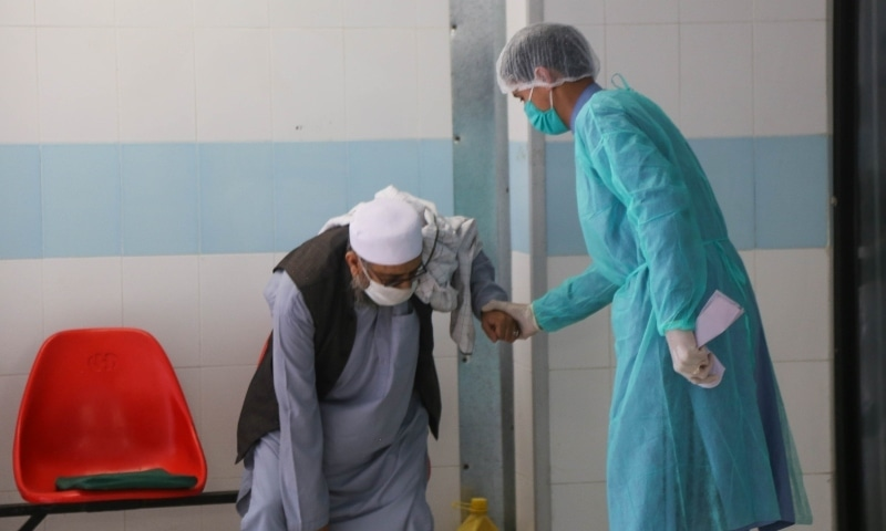 Lift operator Asad Iqbal helps a patient to the Covid-19 isolation ward. — Photo courtesy Fazal Khaliq