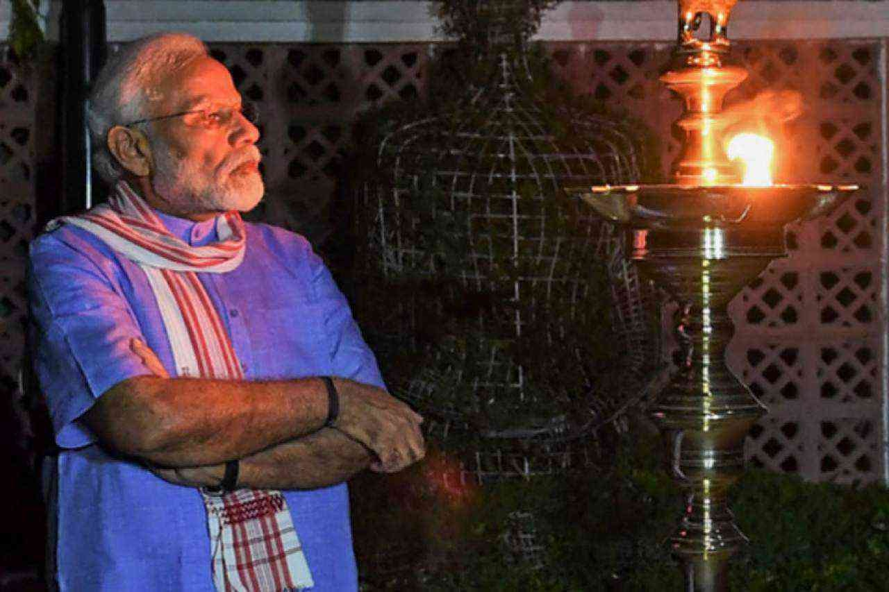 Narendra Modi lights a lamp on April 5. — @PMOIndia via Twitter