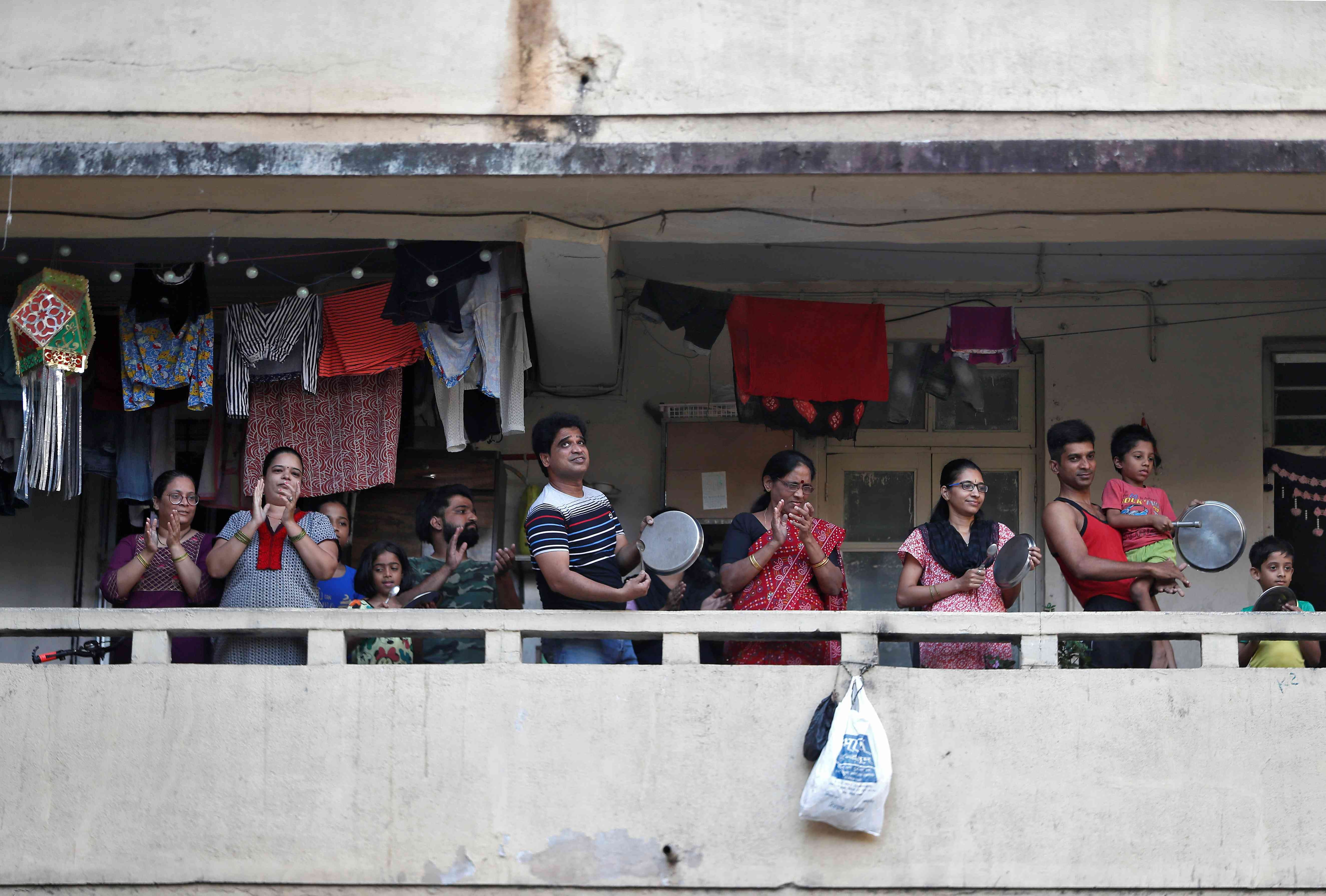 Mumbai residents clap and bang utensils from their balconies on March 22 to cheer for emergency personnel and sanitation workers who are on the frontlines in the fight against coronavirus. — Reuters