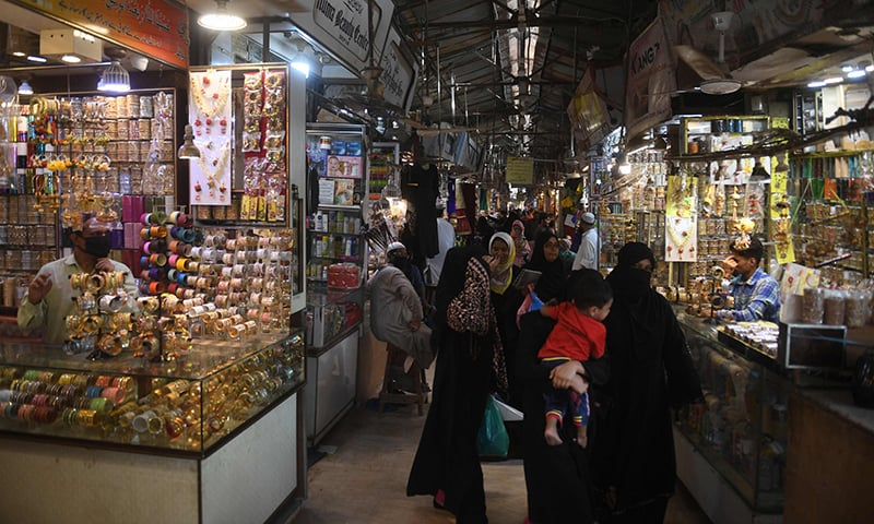 People shop in a market in Karachi on May 11. — AFP