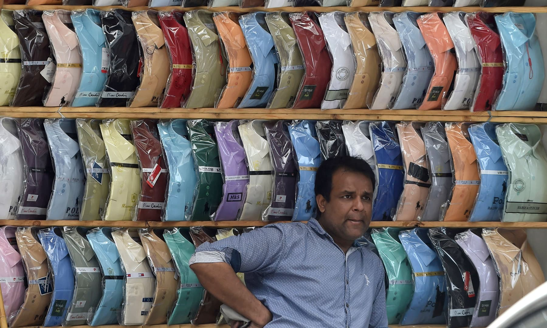 A shopkeeper waits for customers in a market after the government in Lahore on May 11. — AFP