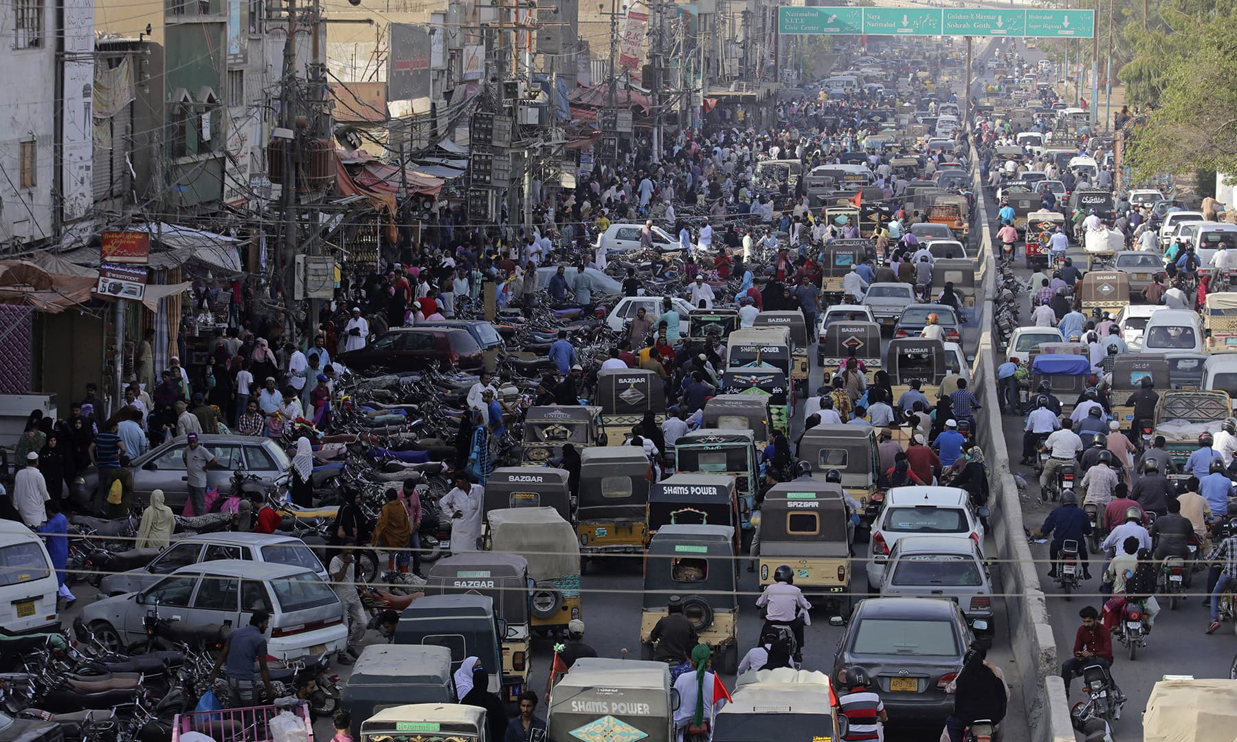People rush to shop at markets in Karachi, Monday. — AP