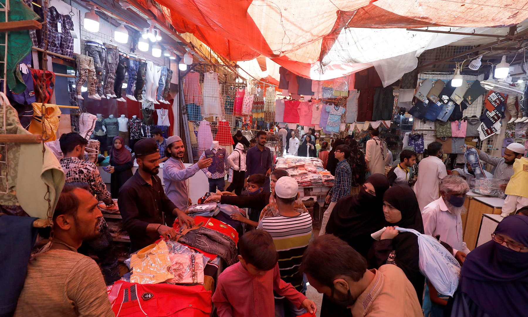 People shop from stalls in a market in Karachi. — Reuters
