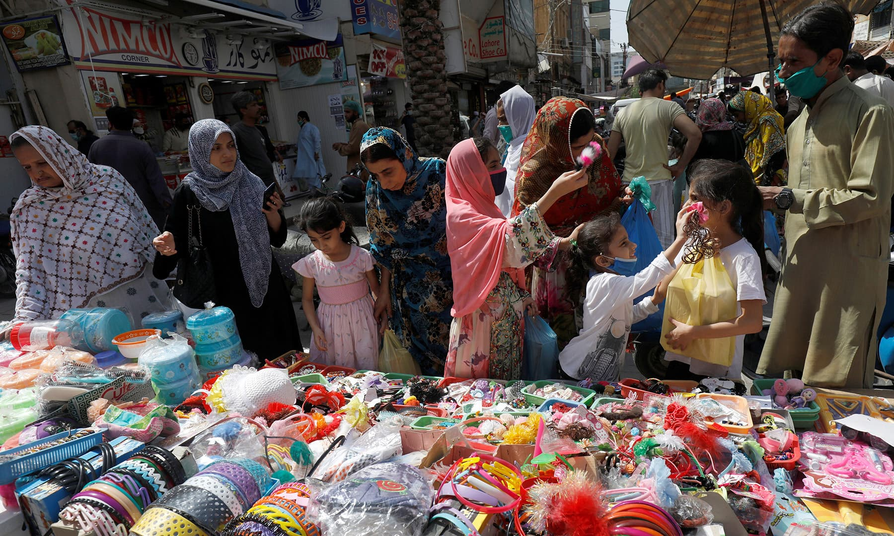 Women and children shop from a stall in a market in Karachi, May 11. — Reuters