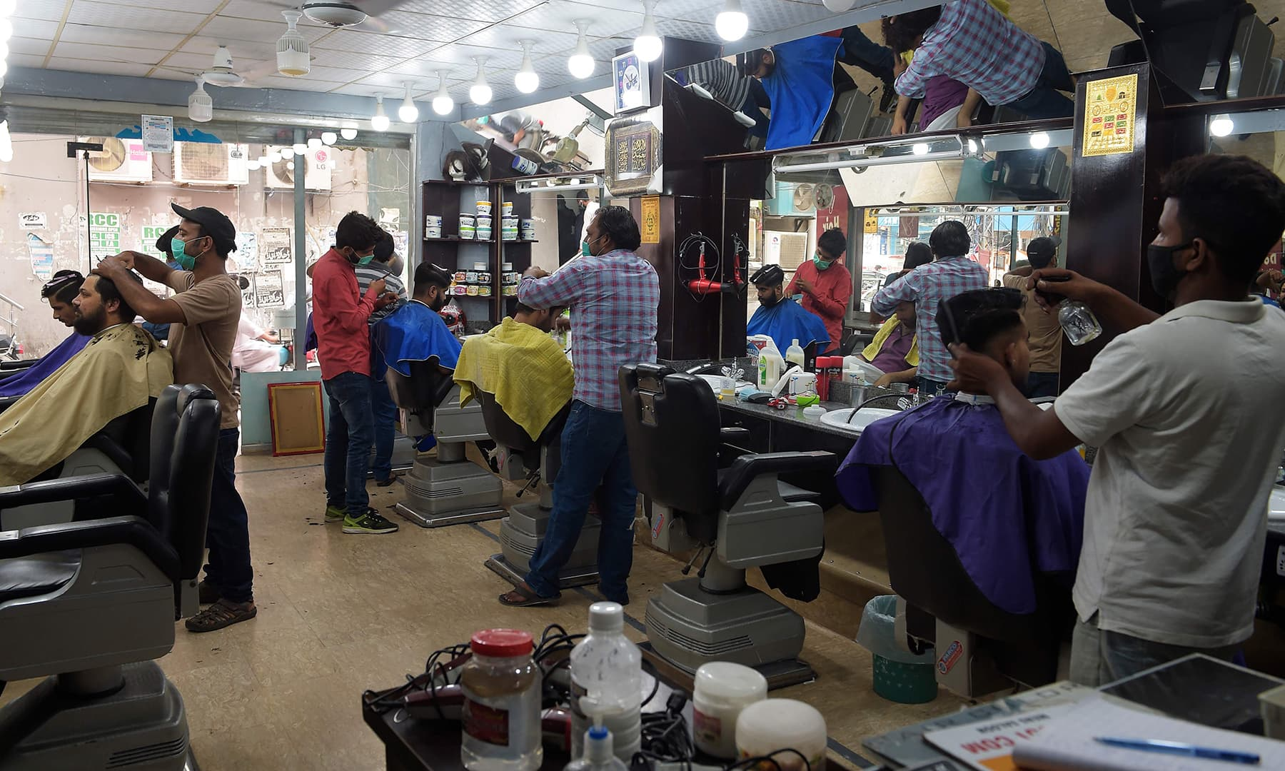 Barbers give haircuts to customers in Rawalpindi. — AFP