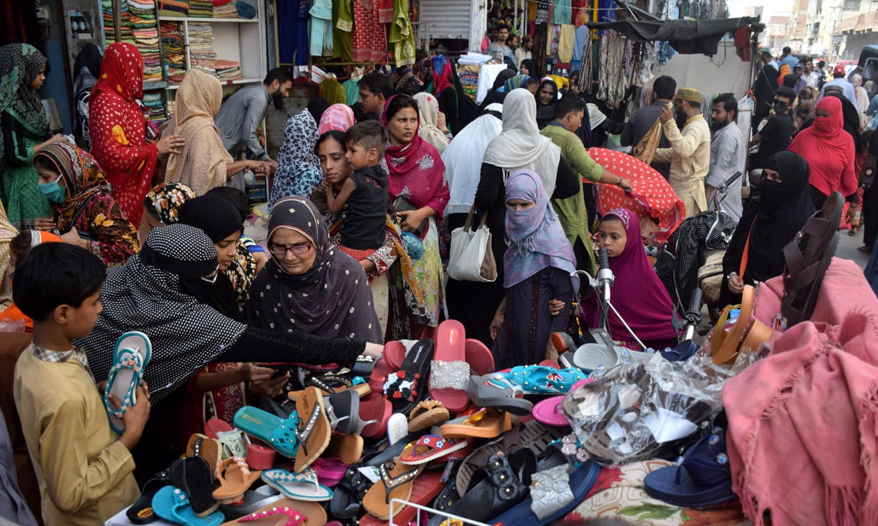 Women shop for shoes at a market in Hyderabad on Monday. — Photo by Umair Ali