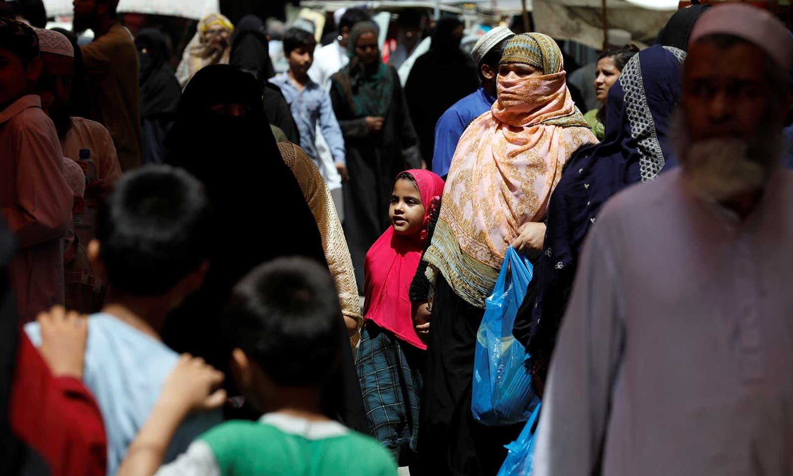 کراچی میں خواتین و بچوں کی بڑی تعداد ماسک کے بغیر بازاروں میں گھومتی نظر آئی— فوٹو: اے ایف پی