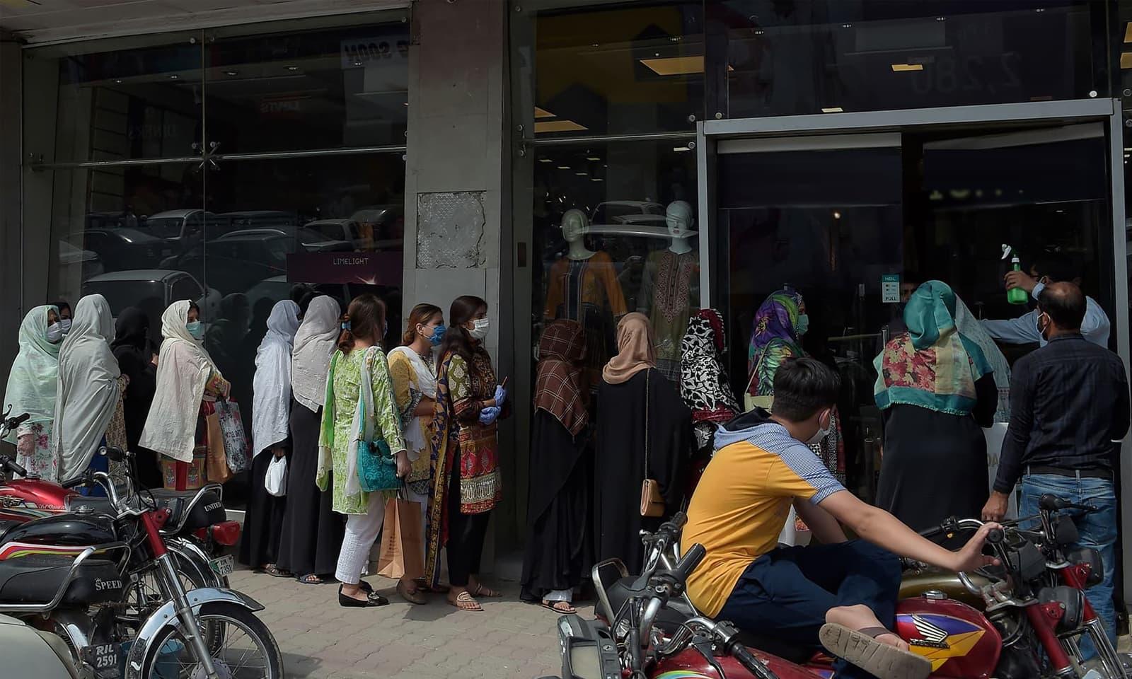 شہر کے اکثر مقامات اور بڑی بڑی دکانوں پر خریداری کے لیے عوام کی قطاریں نظر آئیں اور راولپنڈی کے بازار میں بھی عوام نے احتیاطی تدابیر اختیار نہیں کیں— فوٹو: اے ایف پی