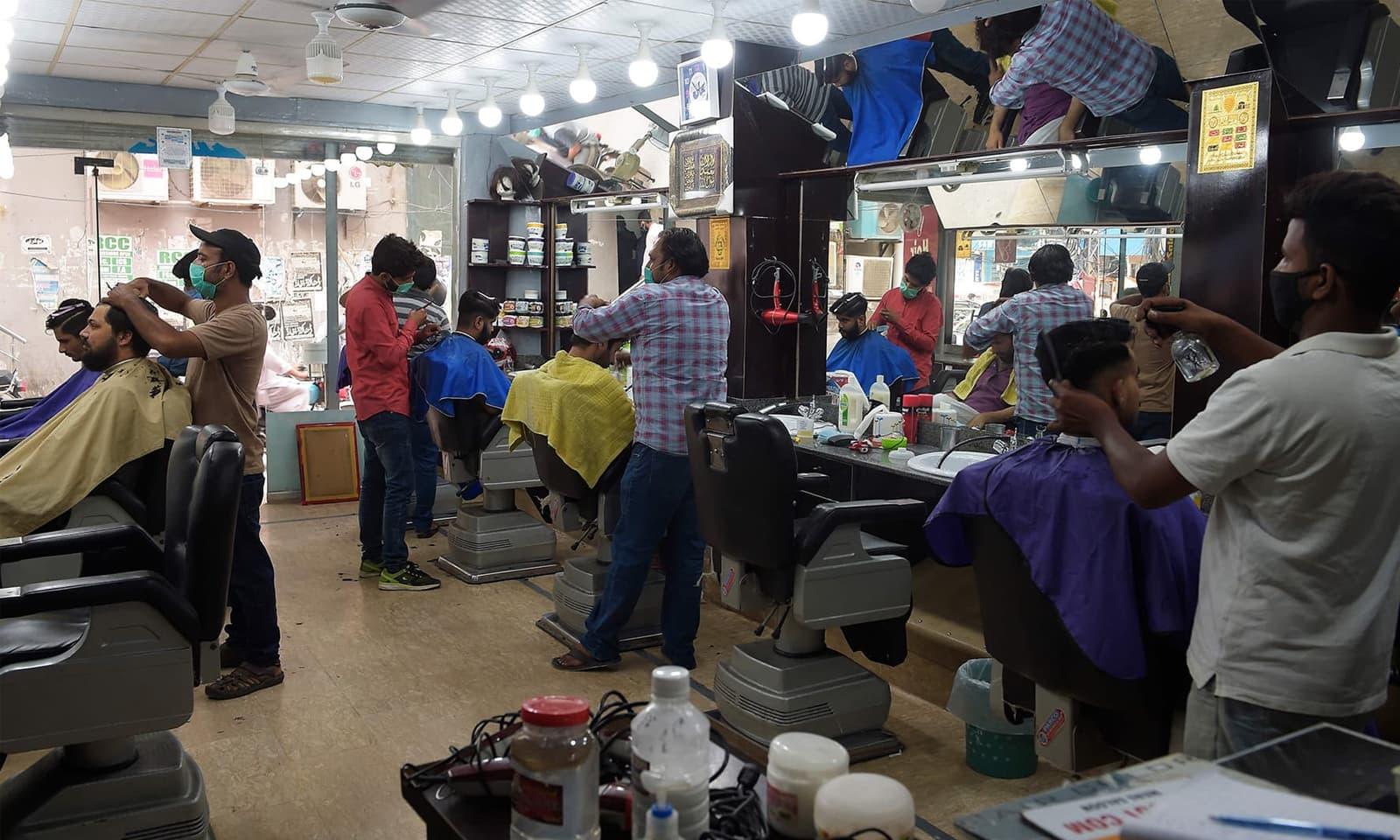 راولپنڈی میں حجام کی دکان پر احتیاطی تدابیر خصوصاً ماسک پہن کر کام کیا جا رہا ہے— اے ایف پی