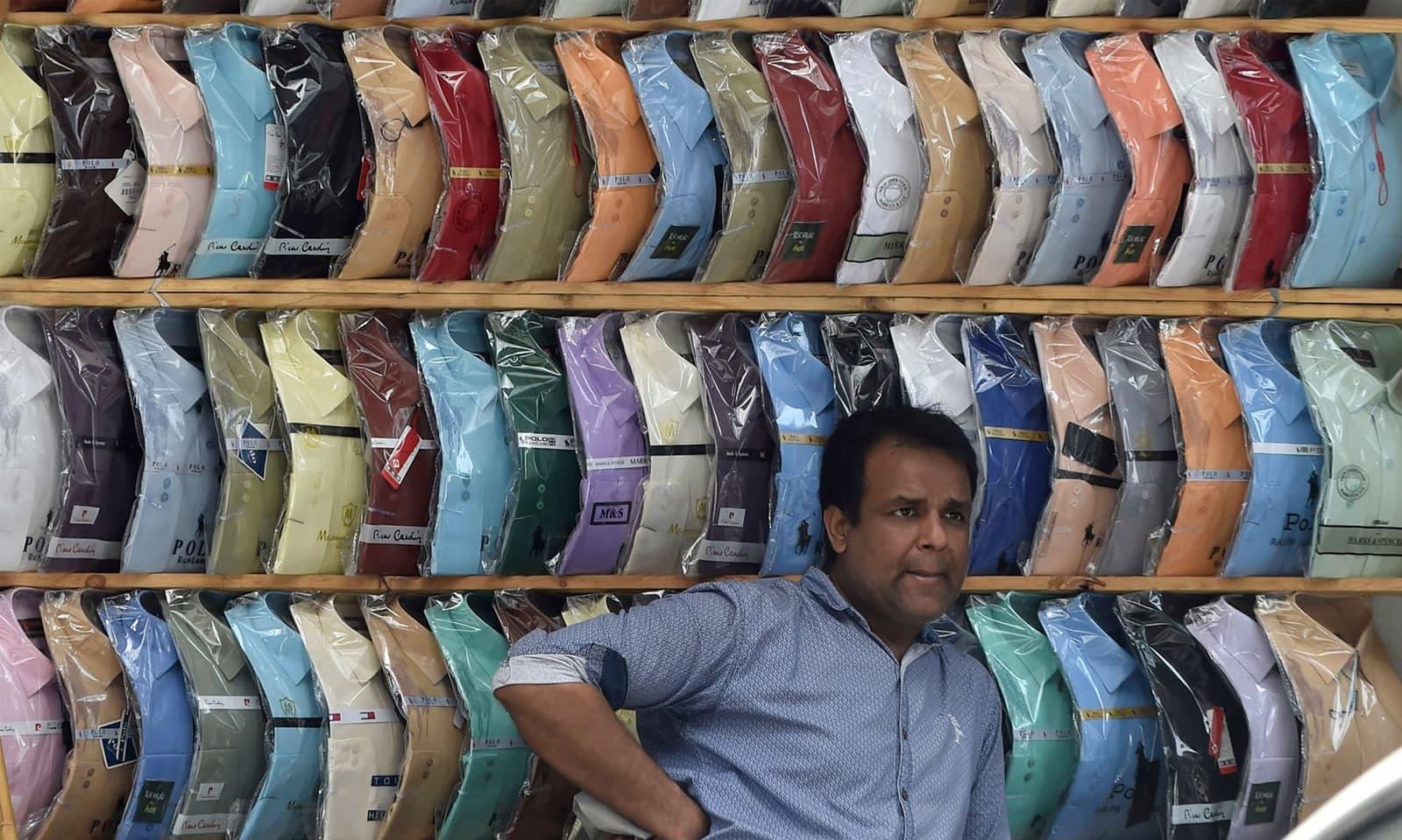 لاہور میں دکاندار لاک ڈاؤن کے بعد دکان پر گاہکوں کا منتظر ہے— فوٹو: اے ایف پی
