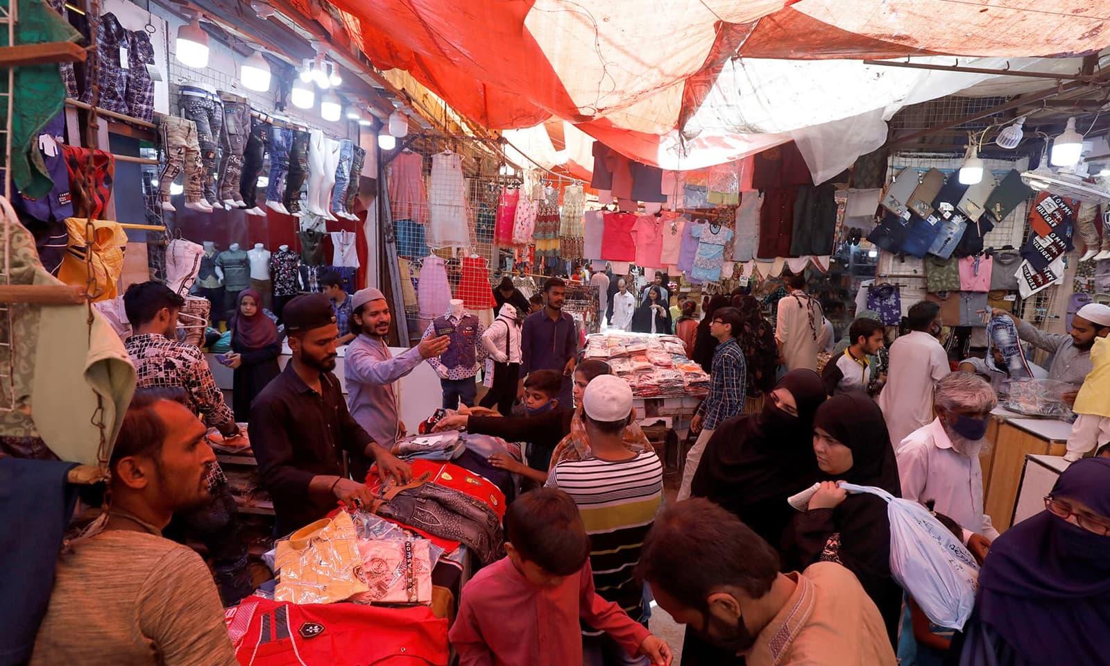 کراچی: دکاندار اور گاہک کی جانب سے احتیاطی تدابیر کی خلاف ورزی کے باوجود قانون نافذ کرنے والے اداروں کی جانب سے کوئی کارروائی نہیں کی گئی— رائٹرز