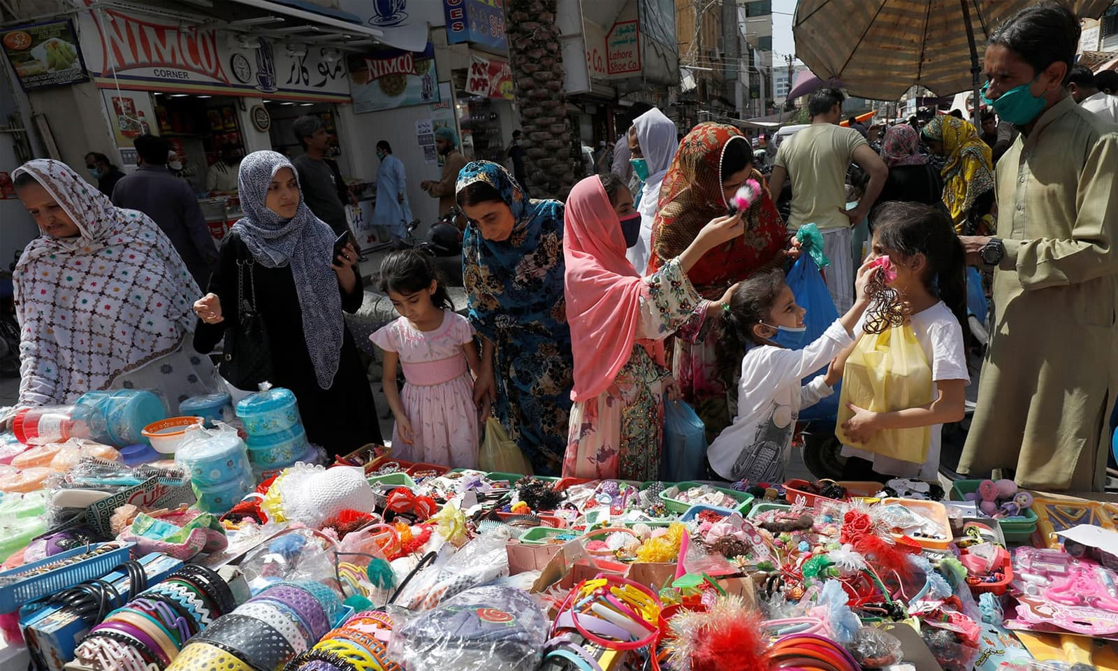 وائرس کے خطرے کے باوجود والدین نے بچوں کے ہمراہ بازاروں کا رخ کیا — فوٹو: رائٹرز