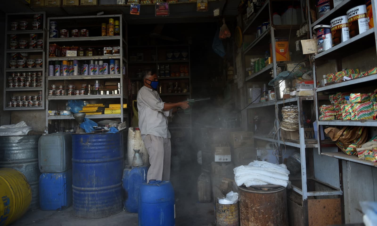 کراچی میں طویل لاک ڈاؤن کے بعد دکان کھولنے والا ایک شخص اپنی دکان کی صفائی کر رہا ہے— فوٹو: اے ایف پی