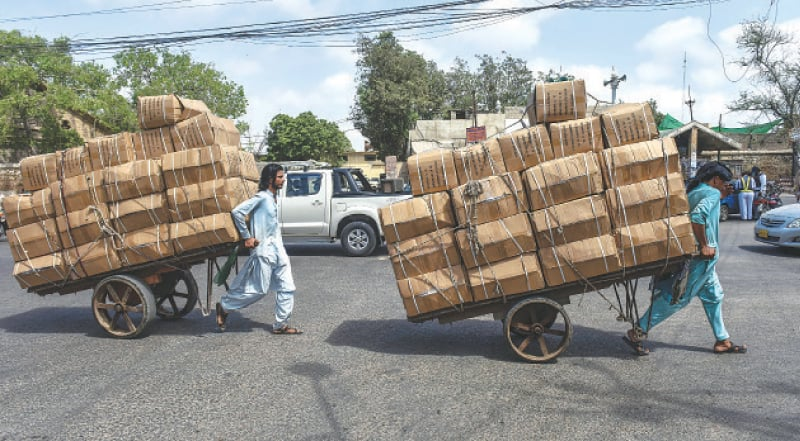 TWO labourers rush with their handcarts loaded at warehouses to replenish shops at Merewether Tower on Monday.—Fahim Siddiqi / White Star