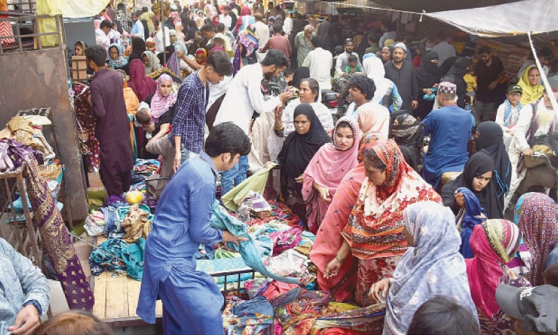 HYDERABAD: People ignore SOPs for social distancing while shopping for Eid at a cloth market on Tuesday as businesses reopen after the government eased the nationwide lockdown.—INP