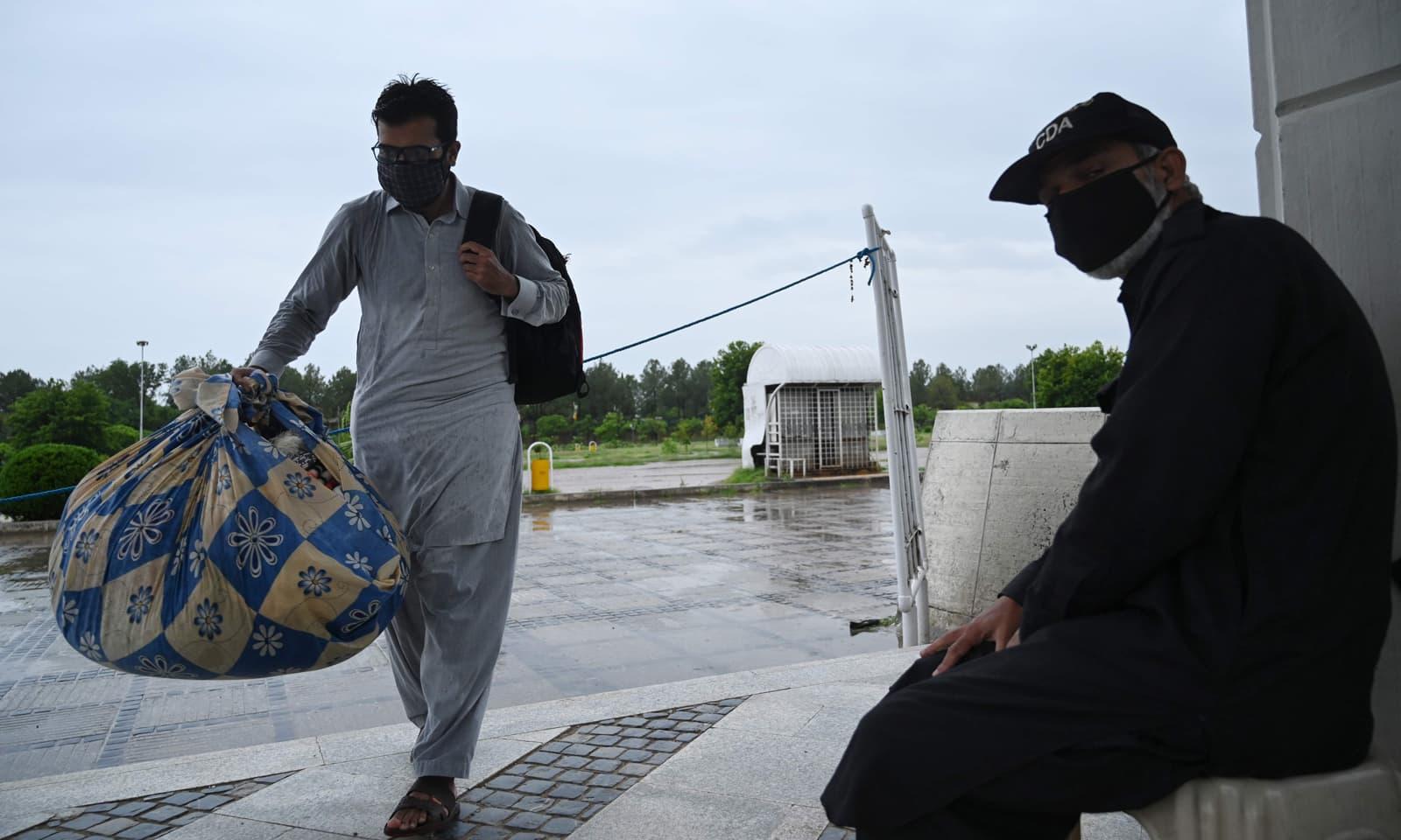 ایک نمازی اپنا سامان اٹھائے اعتکاف کے لیے مسجد میں آرہا ہے— فوٹو: اے ایف پی