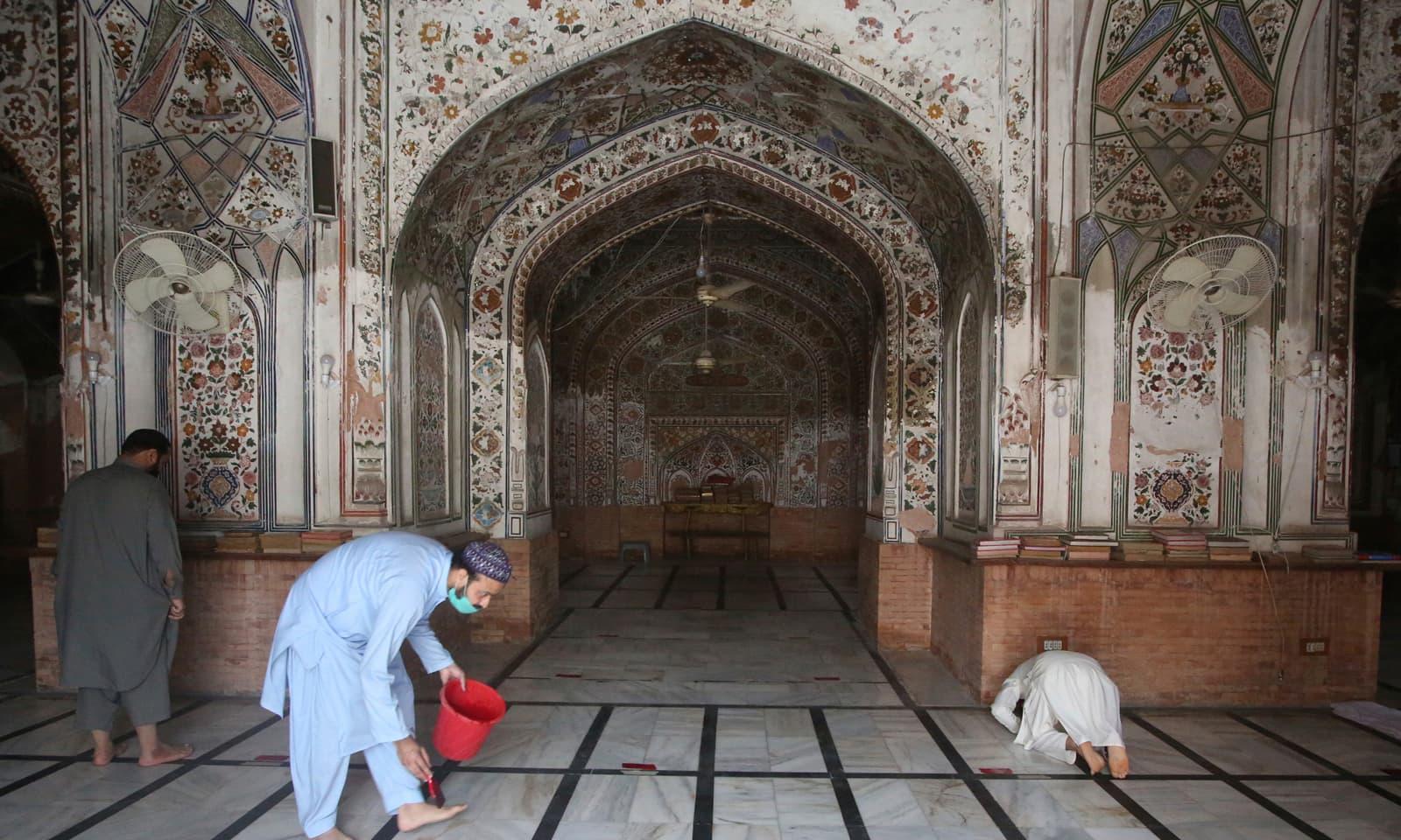 مسجد میں احتیاطی تدابیر کے طور پر نمازیوں کے نماز پڑھے کی جگہ پر نشان لگائے جا رہے ہیں تاکہ سماجی فاصلہ برقرار رکھا جا سکے— فوٹو: اے ایف پی