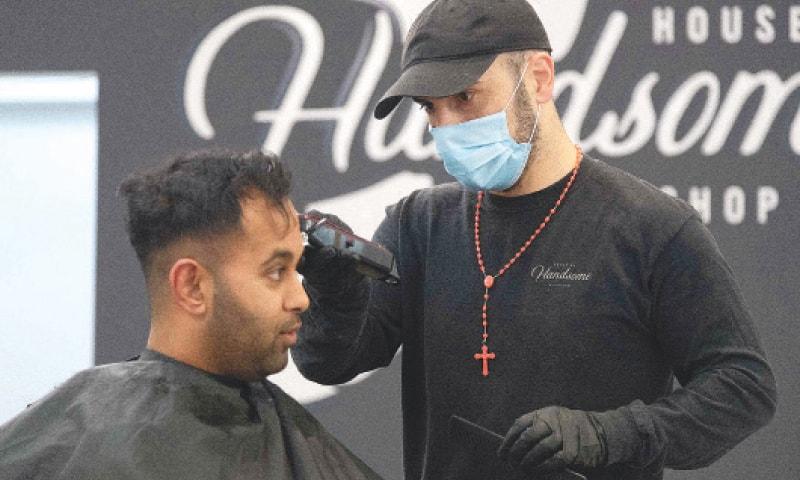 WELLINGTON (New Zealand): A barber wearing a face mask cuts a customer's hair on Thursday.—AFP