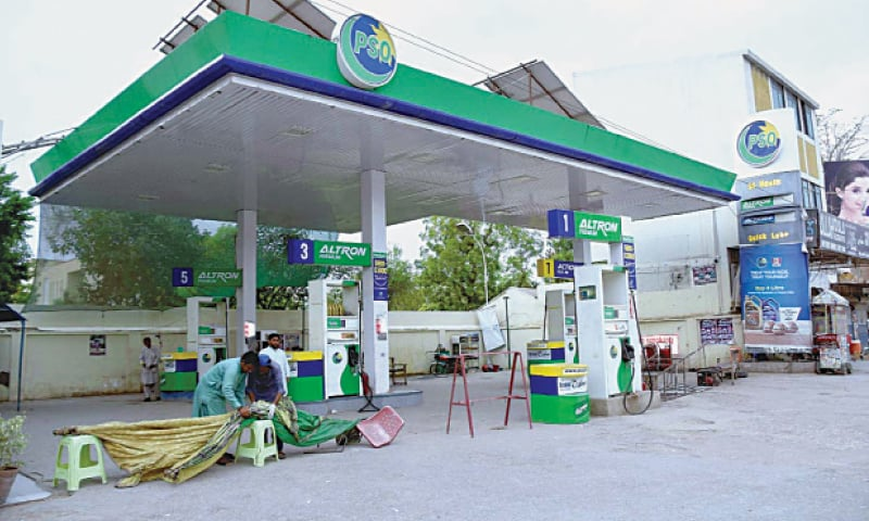 LARKANA:  Workers are seen closing a petrol station. The consumption of petrol and diesel plunged in April as commercial and private transport came to a standstill due to strict countrywide enforcement of lockdown.