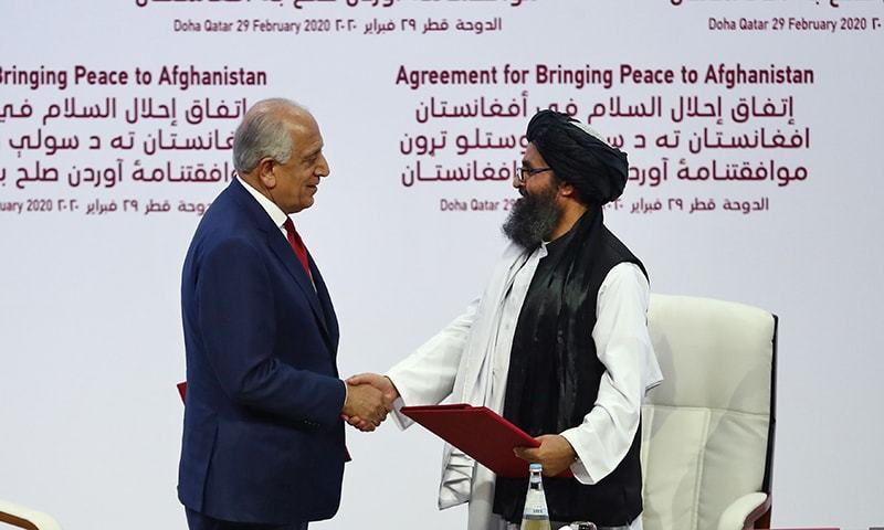 (L to R) US Special Representative for Afghanistan Reconciliation Zalmay Khalilzad and Taliban co-founder Mullah Abdul Ghani Baradar shake hands after signing a peace agreement during a ceremony in the Qatari capital Doha on February 29, 2020. - The United States signed a landmark deal with the Taliban, laying out a timetable for a full troop withdrawal from Afghanistan within 14 months as it seeks an exit from its longest-ever war. Pompeo called on the Taliban to honour its commitments to sever ties with jihadist