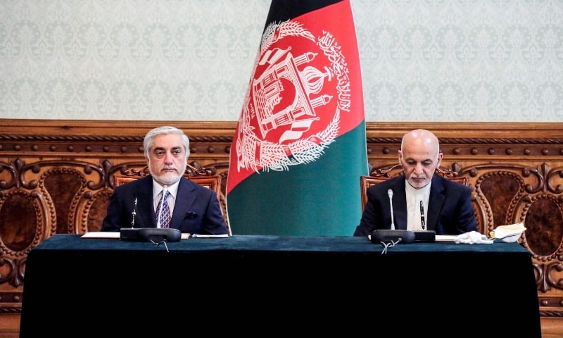 In this handout photograph taken on May 17, Afghan President Ashraf Ghani (R) and his rival Abdullah Abdullah (L) pose for photographs ahead of signing a power-sharing deal agreement at the Presidential Palace in Kabul. — AFP
