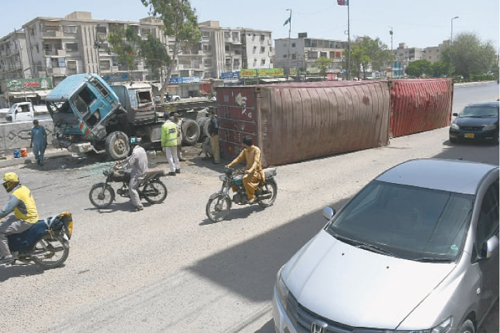 A CLEAR proof of rash driving, a trailer truck lies crippled on the road at Aisha Manzil on Sunday morning with its shipping containers thrown away .—Faysal Mujeeb / White Star