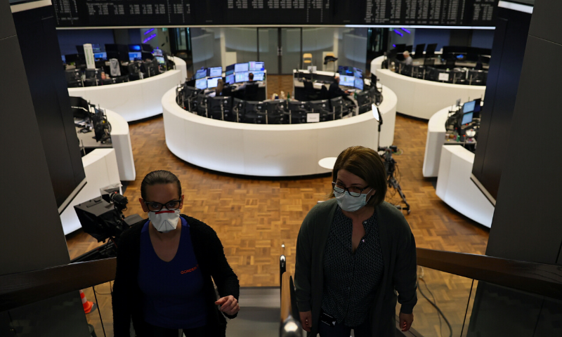 Women wear face masks at Frankfurt's stock exchange as markets react on Covid-19, at the stock exchange in Frankfurt, Germany.— Reuters