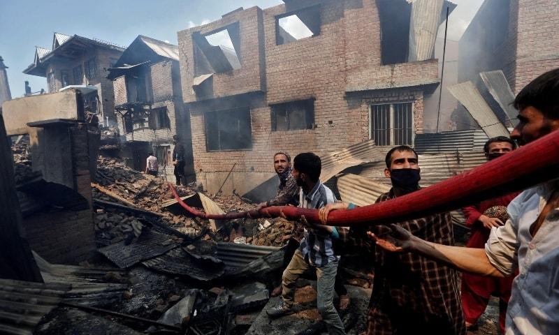 People hold a hosepipe amidst the smoldering debris of residential houses in Srinagar on May 19. — Reuters