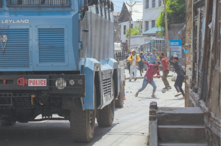 SRINAGAR: Young men throw rocks and bricks at vehicles belonging to Indian paramilitary personnel as they leave the site of a gun battle on Tuesday.—AP