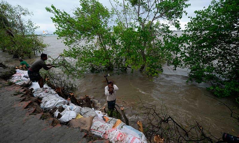 بنگلہ دیش میں کھلنا کے ساحلی علاقے کے رہائشی مٹی سے بند بنانے کی کوشش کر رہے ہیں— فوٹو: اے ایف پی