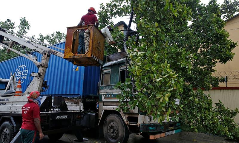 بھارت کے ساحلی شہر کولکتہ میں رضاکار ایک ٹرک پر گرنے والے درخت کو ہٹانے کی کوشش کر رہے ہیں— فوٹو: رائترز