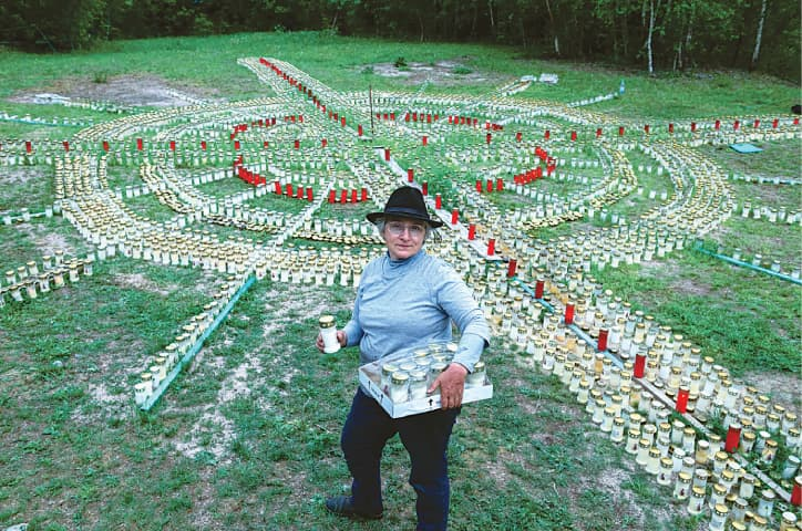 ZELLA MEHLIS (Germany): Gertrud Schop lights candles arranged in the shape of a cross, with one candle dedicated to each of the more than 8,000 German Covid-19-related victims. The 60-year-old Schop plans to continue the work until a vaccine is available.—AFP