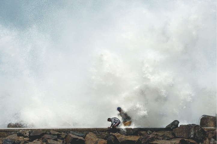 Chennai: Men walk past as waves hit a breakwater at a fishing harbour on Wednesday while Cyclone Amphan barrels towards India's eastern coast.—AFP