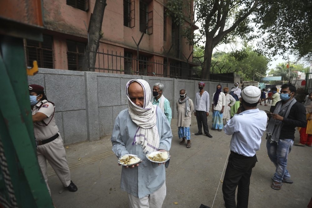 An impoverished man walks after receiving food prepared by the Bangla Sahib Gurdwara kitchen as others wait in a queue in New Delhi, India, May 10. — AP