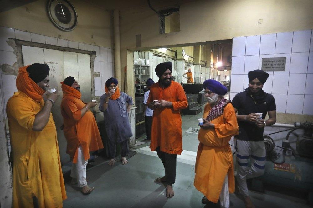 Sikh volunteers take a tea break in the kitchen hall of the Bangla Sahib Gurdwara in New Delhi, India, May 10. — AP