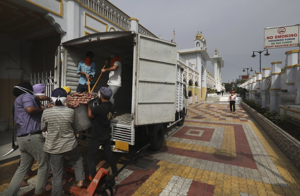 Sikh volunteers help to load food in a van from the kitchen hall of the Bangla Sahib Gurdwara for distribution, in New Delhi, India, May 10. — AP