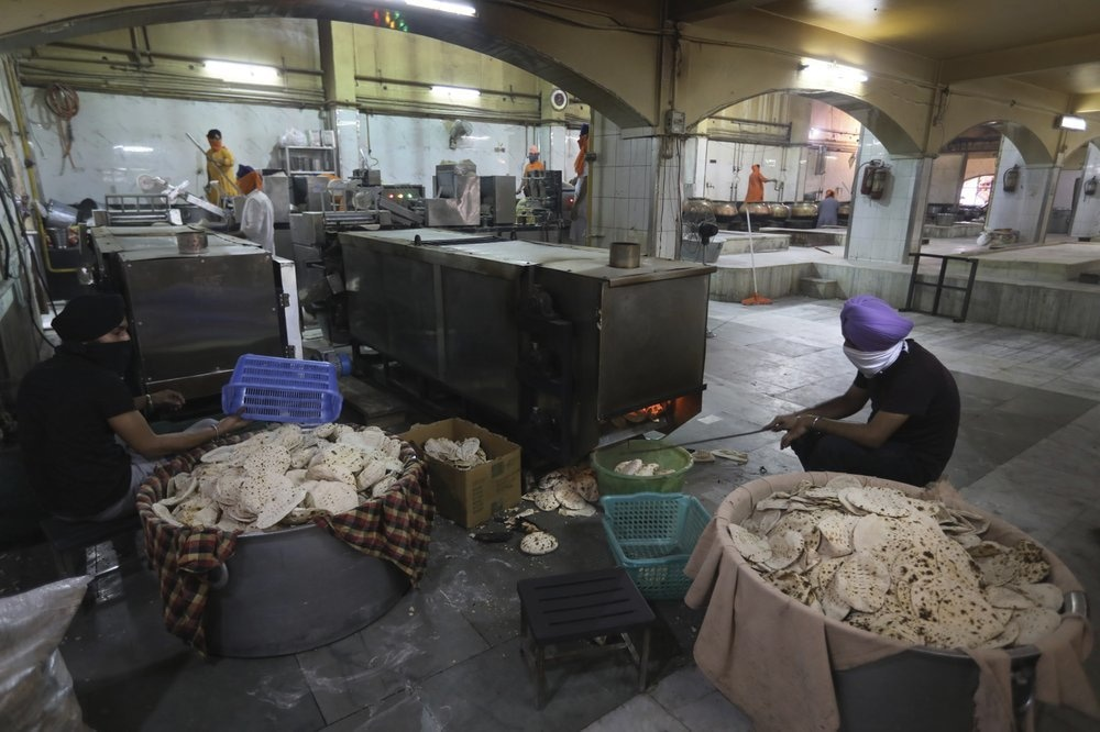 Sikh volunteers take out cooked chapatis from a machine in the kitchen hall of the Bangla Sahib Gurdwara in New Delhi, India, May 10. — AP
