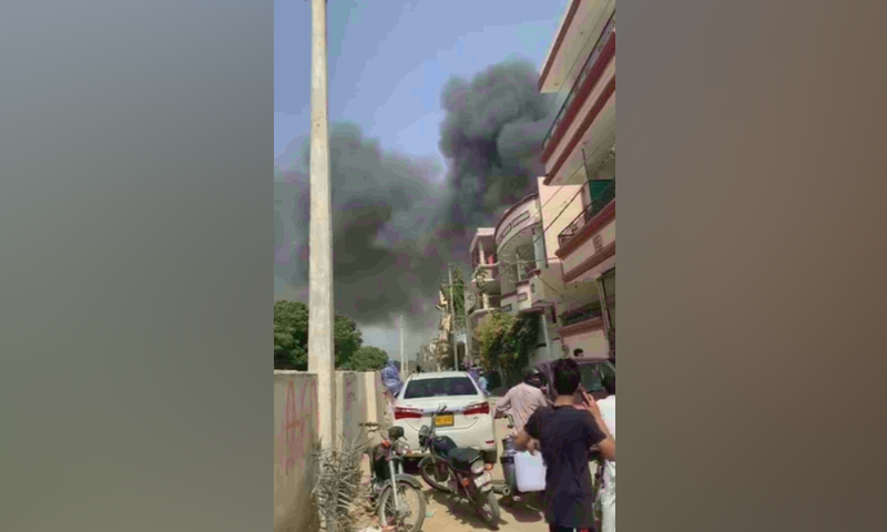 Plumes of smoke can be seen rising from the site of the crash. — DawnNewsTV