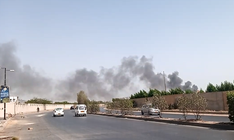 Plumes of smoke can be seen rising from the site of the crash in Karachi. — DawnNewsTV