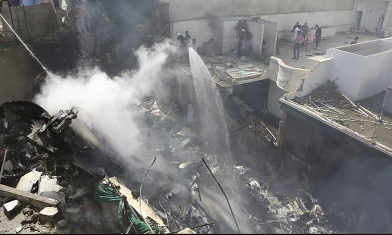 Fire brigade staff try to put out fire caused by plane crash in Karachi on Friday. — AP