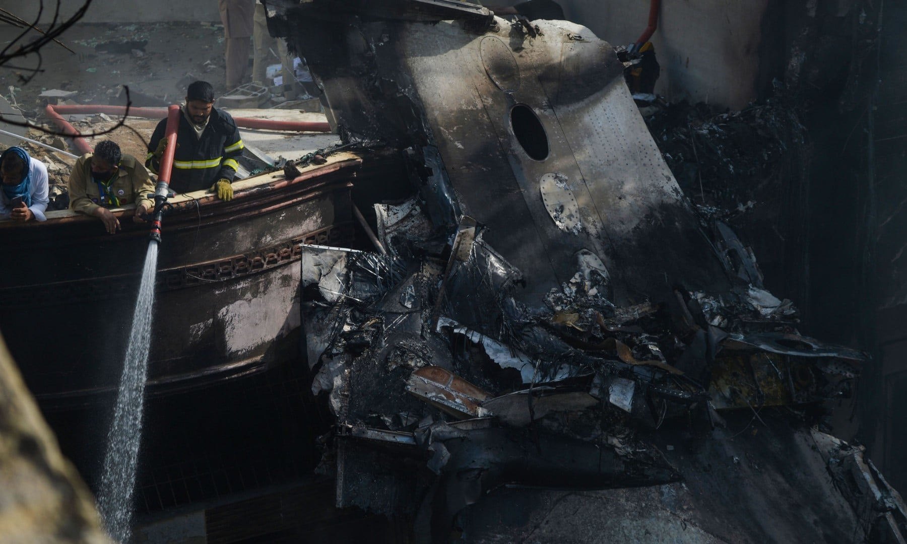 A firefighter sprays water on the wreckage of a Pakistan International Airlines aircraft after it crashed in a residential area in Karachi on May 22. — AFP