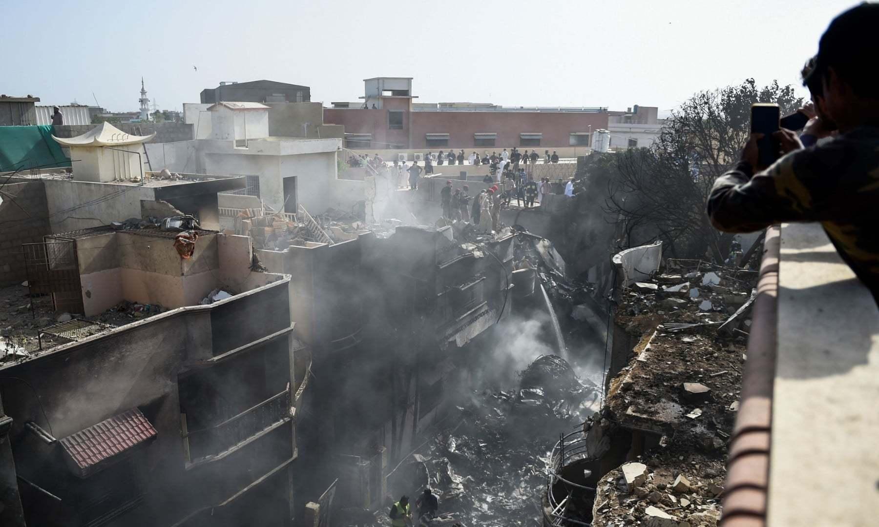 پی آئی اے کا جہاز رہائشی علاقے میں گرا اور گھروں میں بھی آگ لگی—فوٹو:اے ایف پی