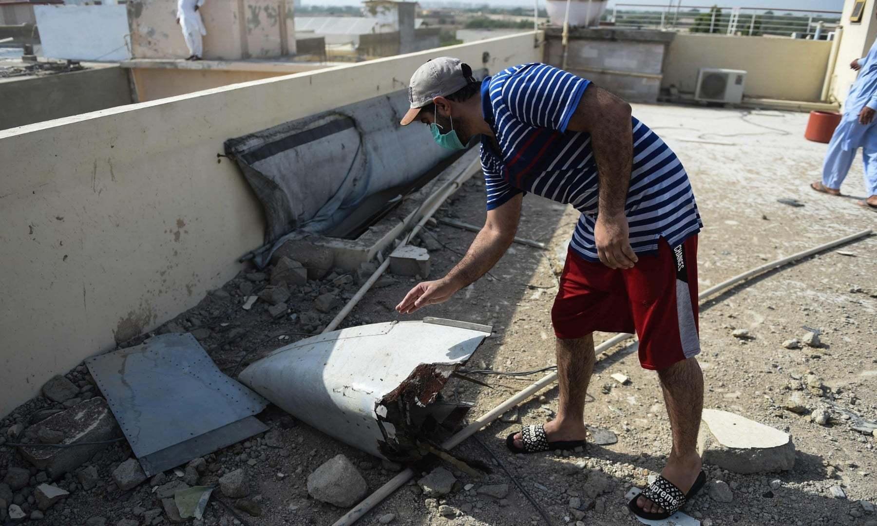 جہاز کے ٹکڑے گھروں کی چھتوں پر بکھرے پڑے ہیں—فوٹو:اے ایف پی