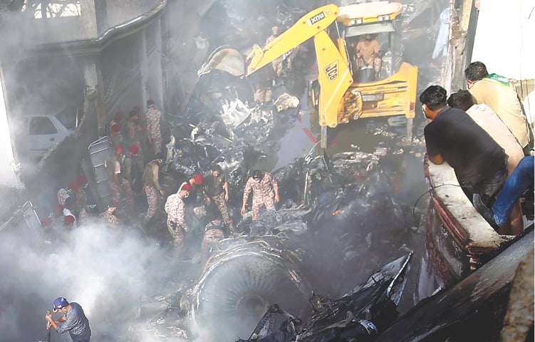HEAVY machinery removes debris at the site of the tragedy on Friday.—Shakil Adil/White Star