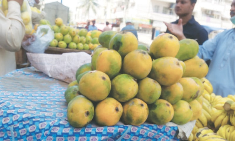 KARACHI: a man purchases mangoes from a vendor. The fruit production has been hit due to climate change.—Photo by Fahim Siddiqi/White Star
